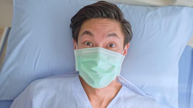 Paciente-joven-asiático-con-máscara-protectora-acostada-en-la-cama-esperando-el-tratamiento-del-médico-en-la-sala-de-recuperación-El-hombre-se-despierta-asustado-y-asustado-sintiendo-pánico-o-nervioso-por-el-mal-sueño