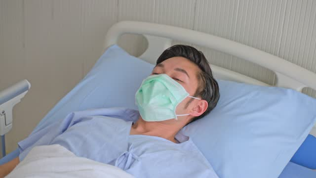 Unwell-young-Asian-male-patient-coughing-while-rest-lying-in-hospital-bed-recovery-after-fell-ill-with-cold-and-flu-Wearing-face-mask-in-quarantine-for-protection-during-covid-19-wait-for-treatment-