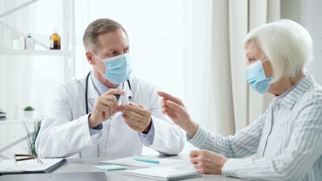 Evite-enfermarse-Médico-masculino-de-mediana-edad-que-usa-máscara-consultando-a-la-mujer-paciente-de-edad-avanzada-sosteniendo-y-mostrando-una-botella-de-vidrio-de-la-vacuna-sentado-en-la-mesa-en-su-oficina
