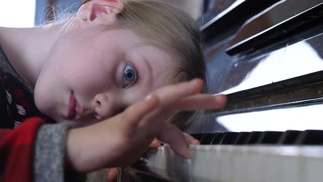 Atractivo-niño-estudia-melodía-musical-en-lección-de-piano