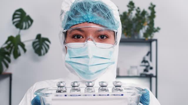 Esperanza-luchando-contra-el-coronavirus-Científica-de-laboratorio-multiétnica-grave-en-traje-de-protección-que-muestra-bandeja-con-frascos-de-vacuna-