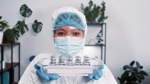 Victoria-sobre-el-coronavirus-La-alegre-trabajadora-del-laboratorio-científico-en-traje-de-protección-muestra-la-bandeja-médica-con-frascos-de-vacuna-