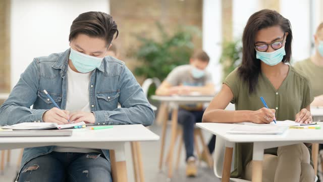 Friends-Diverse-students-sitting-at-table-in-university-wearing-protective-face-mask-writing-test-cheating-and-agree-by-bumping-elbows-in-a-classroom