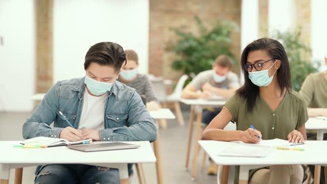 Studieren-der-Zeit-Männliche-Schüler-kommen-in-ein-Klassenzimmer-mit-Laptop-und-Notebooks-stoßen-Ellbogen-mit-seinem-Gruppenkameraden-als-Zeichen-der-Begrüßung-Schüler-tragen-schützende-Gesichtsmaske-Schreibtest