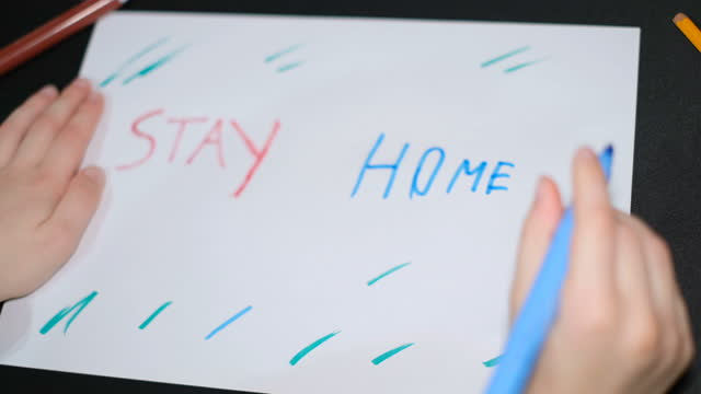 Child-boy-drawing-stay-home-slogan-on-a-paper-in-covid19-pandemic-disease-kids