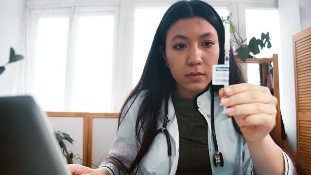 Acercar-a-la-mujer-doctora-multiétnica-profesional-en-bata-de-laboratorio-que-busca-una-nueva-cura-de-jeringa-vacunal-comprobando-con-el-ordenador-portátil-