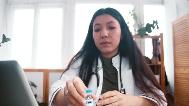 Inspección-de-vacunas-Acercarse-a-la-mujer-doctora-de-farmacia-multiétnica-joven-grave-en-bata-de-laboratorio-mirar-el-matraz-con-medicamentos