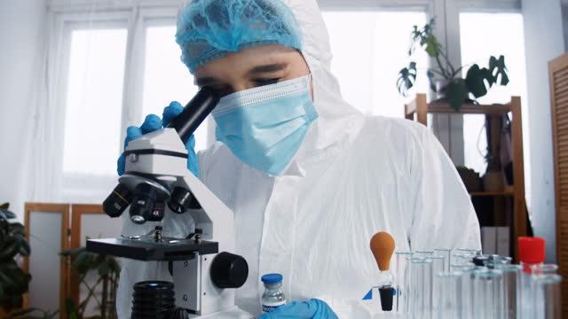 Experto-en-laboratorio-químico-en-el-trabajo-Joven-científico-farmacéutico-enfocado-en-traje-de-protección-utilizando-la-vacuna-de-pruebas-de-microscopio-