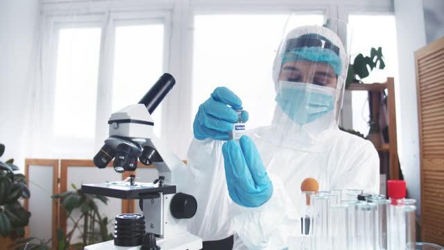 Esperanza-en-la-lucha-contra-las-enfermedades-Una-joven-doctora-profesional-en-traje-de-protección-sostiene-el-matraz-con-una-nueva-vacuna-en-el-laboratorio-de-la-clínica