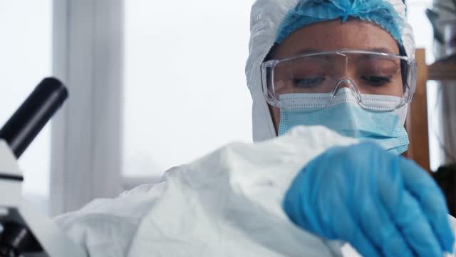 Científico-de-laboratorio-en-el-trabajo-Joven-viróloga-multiétnica-grave-doctora-en-traje-de-protección-sosteniendo-tubo-de-ensayo-con-sangre
