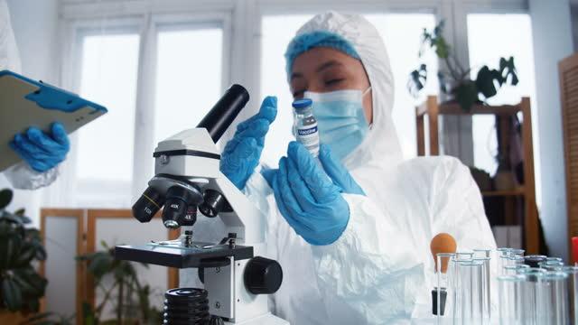 Creación-de-la-vacuna-COVID-19-Dos-mujeres-científicas-de-farmacia-con-trajes-de-protección-completa-prueban-el-nuevo-matraz-curado-en-el-laboratorio-de-la-clínica-