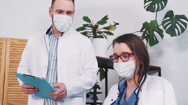 La-joven-farmacéutica-caucásica-firma-papeles-para-colega-masculino-da-frasco-con-vacuna-en-el-consultorio-de-la-clínica-ligera-
