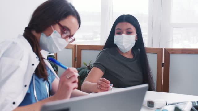 La-joven-doctora-caucásica-consulta-a-una-mujer-paciente-de-raza-mixta-con-máscara-sosteniendo-el-frasco-de-medicamentos-en-el-examen-médico-