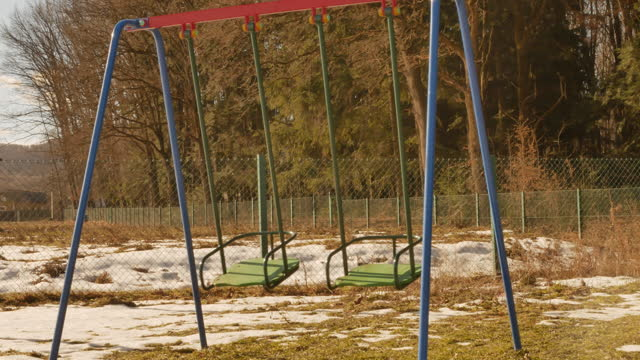 swing-on-a-playground-near-the-forest-wind-is-moving-it-no-kids-