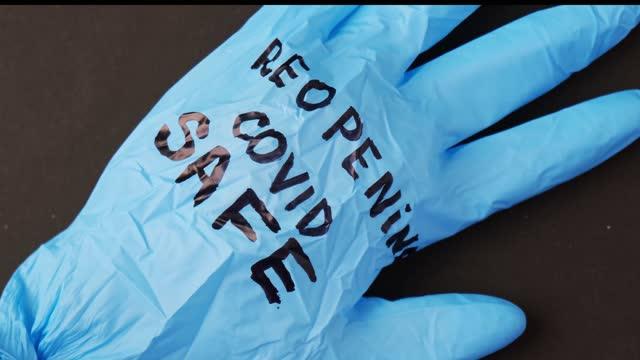 Guante-quirúrgico-de-látex-azul-reventado-sobre-fondo-negro-Reapertura-de-la-caja-fuerte-covid-Abra-de-nuevo-el-texto-escrito-en-guante-médico-Nueva-normalidad