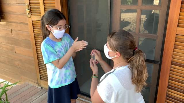 Niña-y-madre-preparándose-en-la-escuela-de-fot-usando-desinfectante-de-manos-y-máscara-facial-protectora-durante-Covid-19-