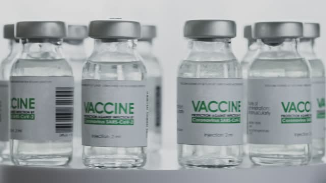 Looped-Bottles-of-vaccine-for-COVID-19-coronavirus-cure-are-quickly-rotated-in-research-lab-Vaccination-injection-clinical-trial-during-pandemic-Flasks-vials-are-spinning-counterclockwise-Wide