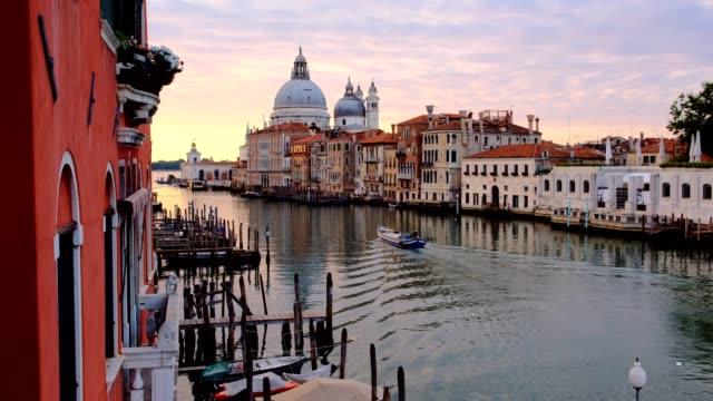 Movimiento-barrido-de-pasar-lancha-Vista-del-hermoso-amanecer-del-Gran-Canal-y-Basilica-di-Santa-Maria-della-Salute-