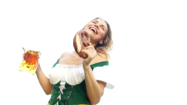 A-beautiful-dancing-girl-dressed-in-Oktoberfest-costume-of-Bavaria-holds-a-beer-mug-and-a-traditional-Bavarian-pretzel-The-woman-leans-over-the-camera-the-bottom-view-Dance-to-Oktoberfest