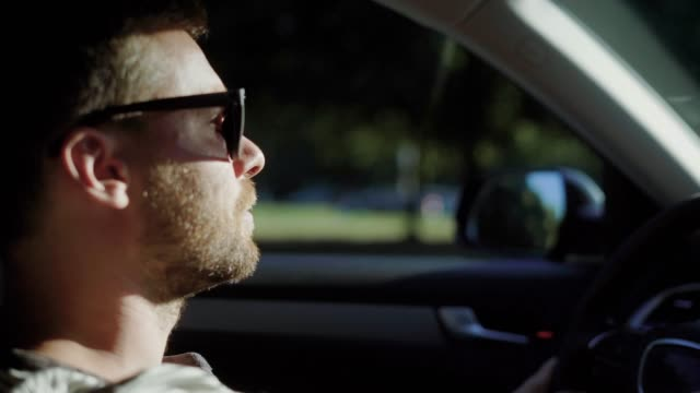 A-man-is-driving-a-modern-car-A-handsome-man-with-a-beard-in-the-sun-protective-glasses-confidently-steers