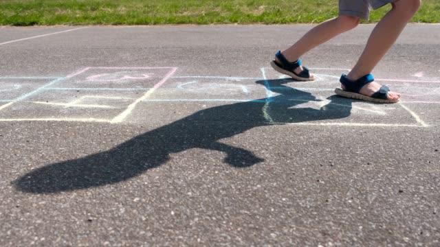 Muchacho-salta-jugando-rayuela-en-la-calle-Piernas-de-primer-plano-Vista-lateral-