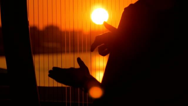 Frauen-Silhouette-spielt-Harfe-bei-Sonnenuntergang