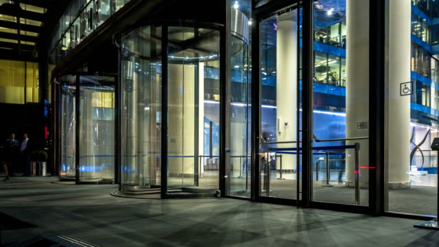 the-flow-of-people-passing-through-the-revolving-door-of-the-modern-office-building-at-the-end-of-the-working-day-time-lapse