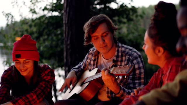 Handsome-young-man-tourist-is-playing-the-guitar-and-smiling-while-his-friends-are-singing-and-having-fun-resting-around-fire-near-lake-or-river-Green-trees-are-visible-
