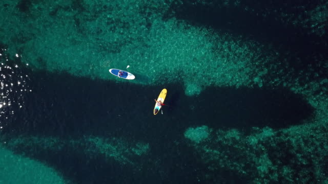 Video-from-above-aerial-view-of-two-people-on-a-stand-up-paddle-(SUP)-in-Sardinia-Italy-