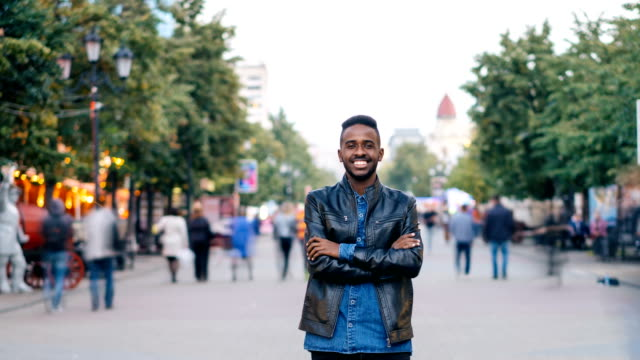 Time-lapse-portrait-of-handsome-man-African-American-student-looking-at-camera-and-smiling-standing-in-the-street-downlown-while-people-are-whizzing-around-him-