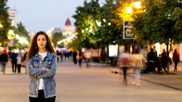 Time-lapse-of-unhappy-girl-standing-alone-on-beautiful-pedestrian-street-late-in-the-evening-and-looking-at-camera-when-people-are-whizzing-around-Society-and-loneliness-concept-