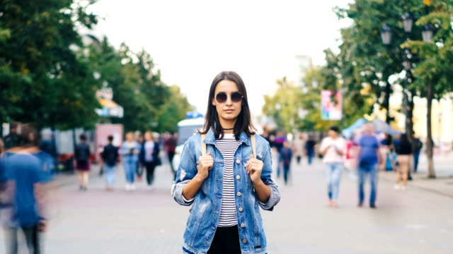 Time-lapse-retrato-de-atractiva-morenaza-en-gafas-de-sol-de-pie-en-la-calle-solita-y-mirando-a-cámara-cuando-hombres-y-mujeres-pasan-el-día-de-otoño-