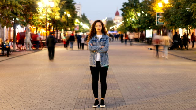Time-lapse-of-attractive-woman-with-long-curly-hair-standing-in-the-street-with-crossed-arms-and-looking-at-camera-on-autumn-evening-when-people-are-moving-around-