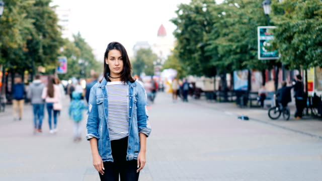 Time-lapse-of-unhappy-lonely-girl-standing-alone-in-the-street-and-looking-at-camera-when-people-are-walking-around-fast-Loneliness-and-modern-life-concept-