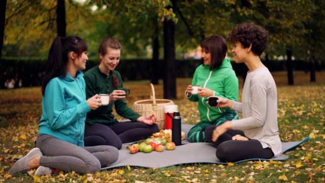 Happy-girls-are-having-picnic-in-park-sitting-on-yoga-mats-and-eating-after-outdoor-practice-in-autumn-girls-are-talking-and-laughing-Communication-and-food-concept-
