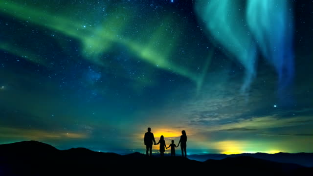 The-family-standing-on-the-rock-on-the-northern-light-background-time-lapse
