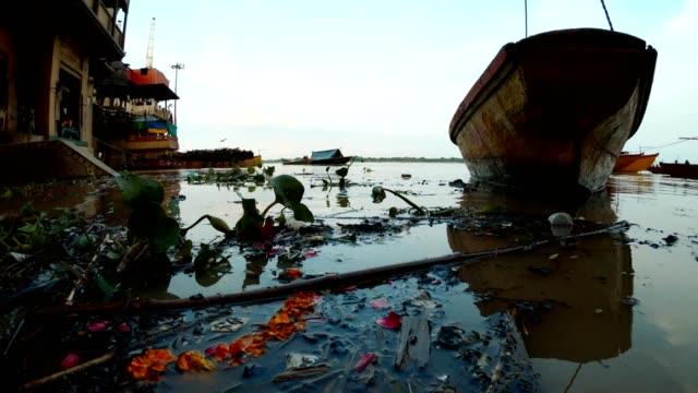 Inundación-en-Manikarnika-Ghat-lugar-de-cremación-de-Varanasi-las-ramas-negras-flotan-en-barco-de-río-en-el-muelle-de-ladridos-lejos-con-leña-y-crematorios-de-gas
