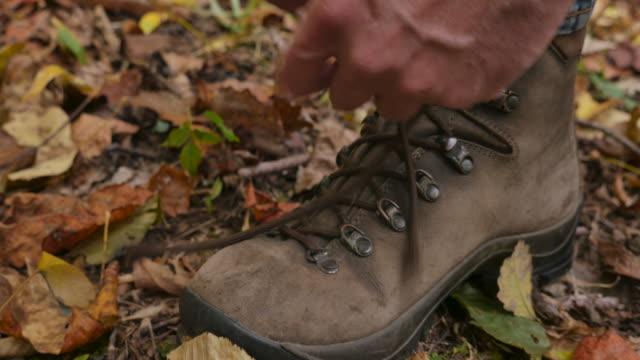 Empuje-de-un-hombre-ateando-sus-botas-de-senderismo-y-luego-se-aleja-en-el-bosque