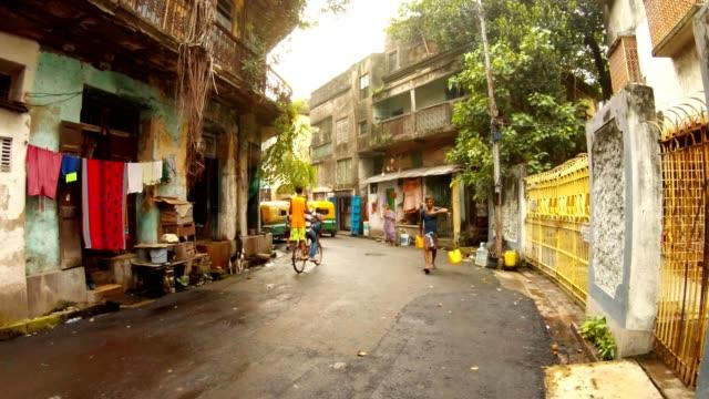 alte-Straße-schäbige-Gebäude-bengalis-Menschen-gehen-tragen-Wasser-Schulmädchen-Jungen-Reiten-Fahrrad-Kolkata