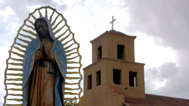 Inclinación-para-revelar-una-estatua-de-la-Virgen-Guadalupe-y-una-iglesia-católica-mexicana