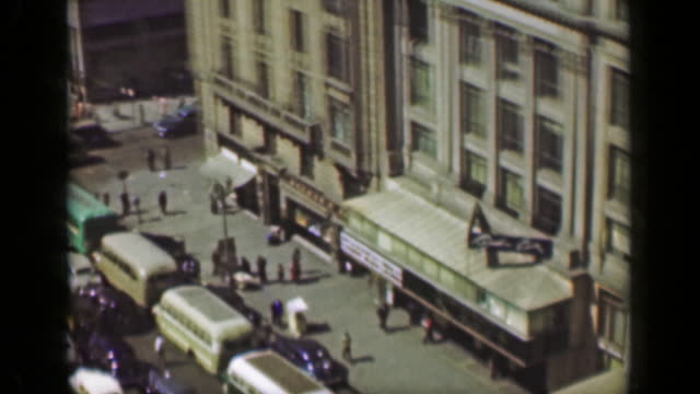 1952:-Downtown-building-architecture-busy-car-traffic-municipal-park-square-