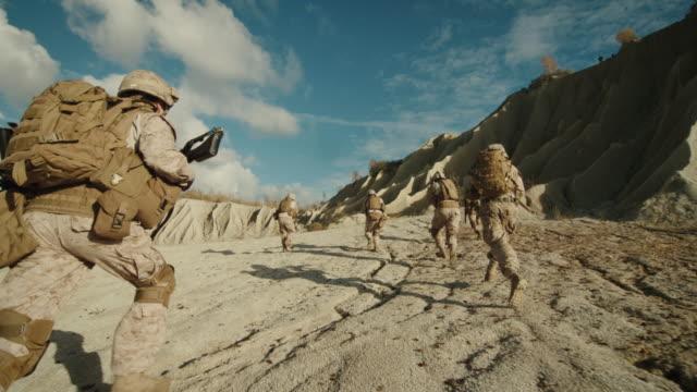 Seguir-el-tiro-de-la-escuadra-de-soldados-corriendo-hacia-adelante-durante-la-operación-militar-en-el-desierto-Cámara-lenta-