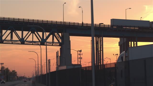 CLOSE-UP:-Silhouette-Autos-und-Lastwagen-fahren-durch-industrielle-Stadt-bei-Sonnenuntergang