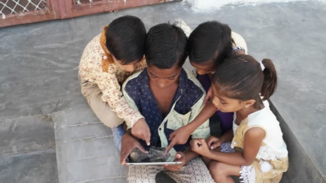 Indian-Kids-busy-on-a-touchscreen-tablet-elder-sibling-teaching-them-close-up-handheld
