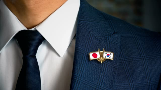 Businessman-Walking-Towards-Camera-With-Friend-Country-Flags-Pin-Japan---South-Korea