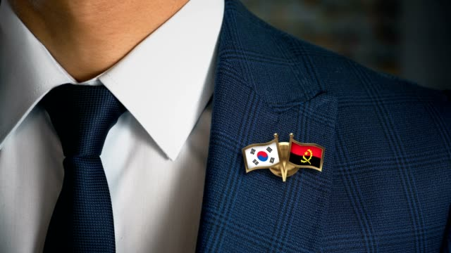 Businessman-Walking-Towards-Camera-With-Friend-Country-Flags-Pin-South-Korea---Angola