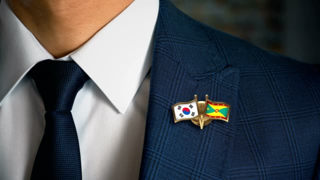 Businessman-Walking-Towards-Camera-With-Friend-Country-Flags-Pin-South-Korea---Grenada