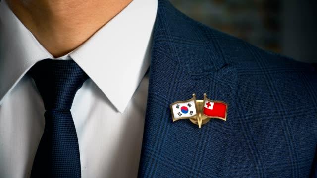 Empresario-caminando-hacia-cámara-con-amigo-país-banderas-Pin-Corea-del-sur---Tonga