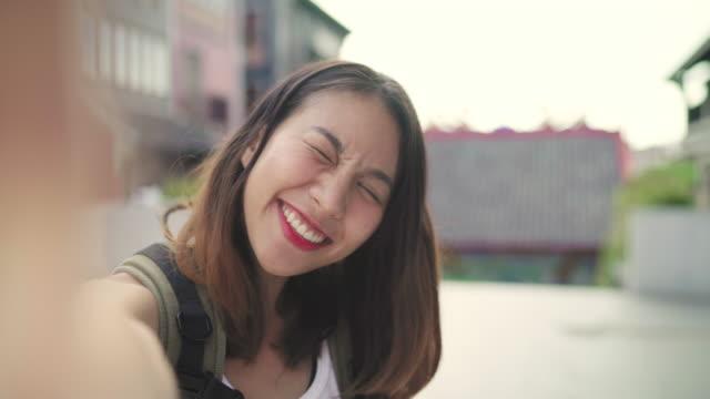 Mujer-de-blogger-alegre-hermosa-joven-asiático-para-mochileros-con-smartphone-tomando-selfie-mientras-viaja-a-Chinatown-en-Beijing-China-Estilo-de-vida-mochila-concepto-de-vacaciones-de-viajes-turísticos-Punto-de-vista-