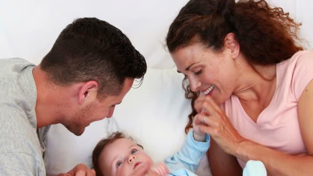 Baby-boy-ser-tickled-los-padres-en-la-cama